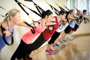 A group of people doing suspension training at the gym.